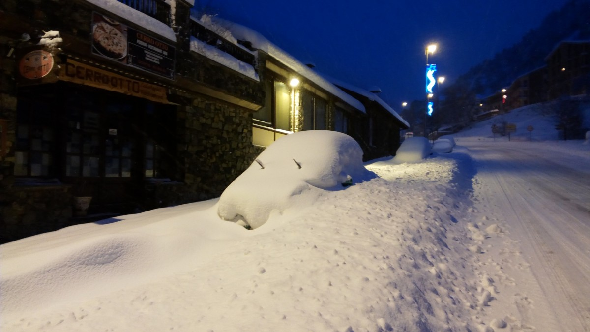 Car completely covered by snow in the main street of Arinsal