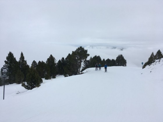 Touring ski in the blue run Cami Inferior with the mountain peaks behind the clouds